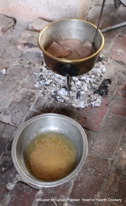 Beef steaks turned with a cooking fork frequently to produce a pale gravy over a burner of embers producing low heat. The gravy is removed and poured in the basin as it is produced.