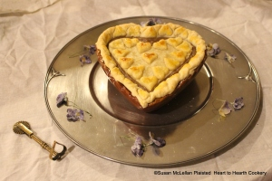 """Pictured is the receipt (recipe) """"Plum Tarts-my Lady Sheldons Receipt"""" as it could be presented to table.  The tart is served on a reproduction 17th century pewter plate surrounded by candied heart's ease.  The heart shaped brass jigger used for the """"cutt"""" paste is to the left."""