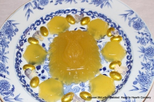 "This is the presentation of the receipt (recipe) ""To make Orange Jelly"" from the pineapple and patty pan molds.  This presentation of the jelly made from the grated rinds of 2 China oranges, 2 lemons and 2 Seville oranges infused in Seville orange juice and jelled with isinglass is garnished with almond comfits gilded with gold leaf."