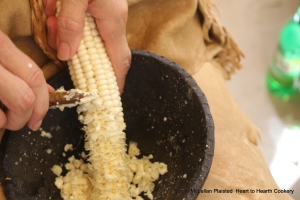 """When Puhwem (Lenape white flour corn) is green corn the kernels are filled with milky white juices that are concentrated corn flavor. I am using my jaspar knife to remove the kernels from the cob to prepare green corn bread. Note all the splatters of """"milk"""" in my bowl and on my finger."""